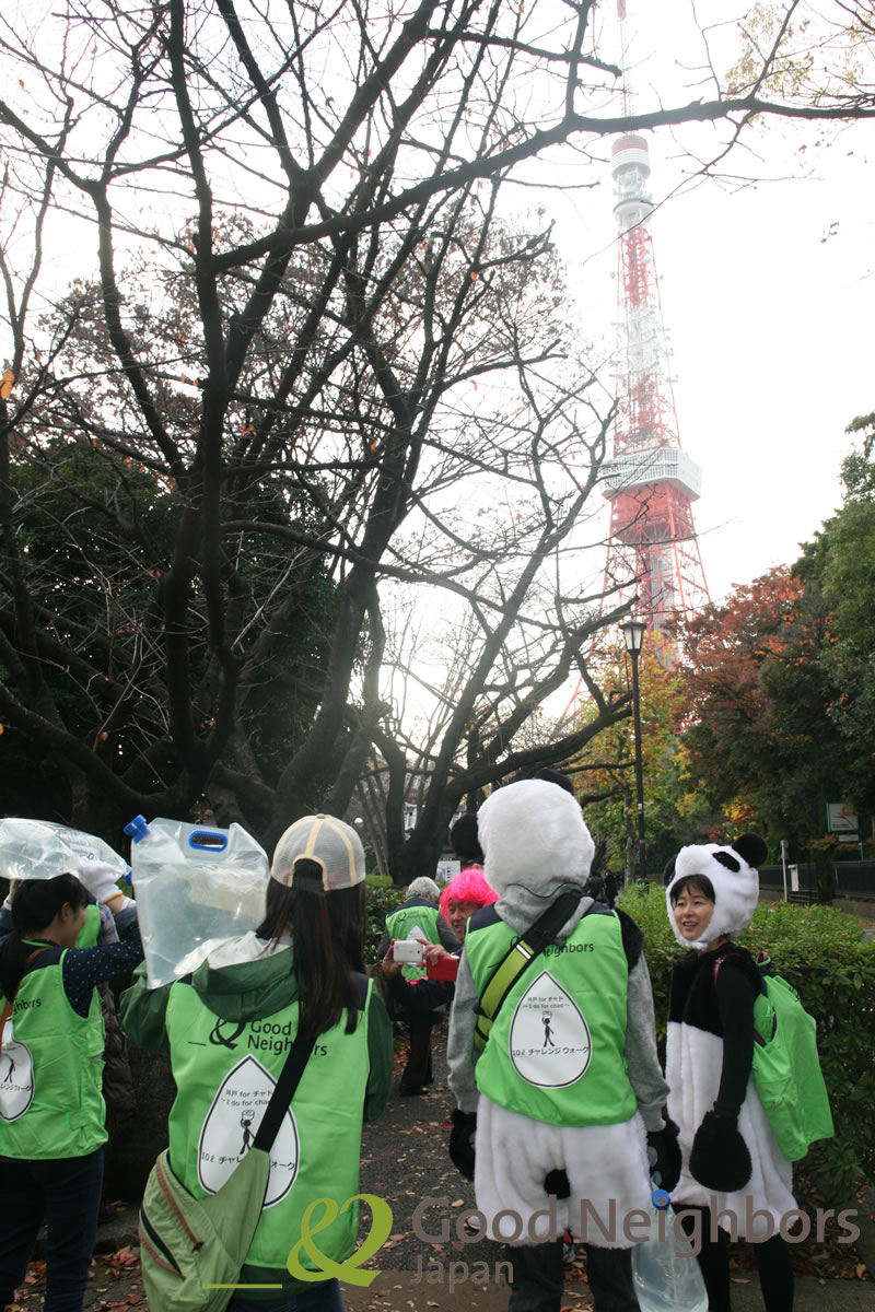 紅葉の美しい増上寺の脇を歩く参加者