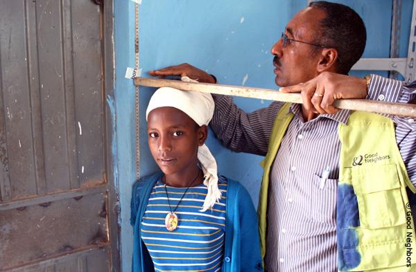 スタッフが少女の身長を測っている様子